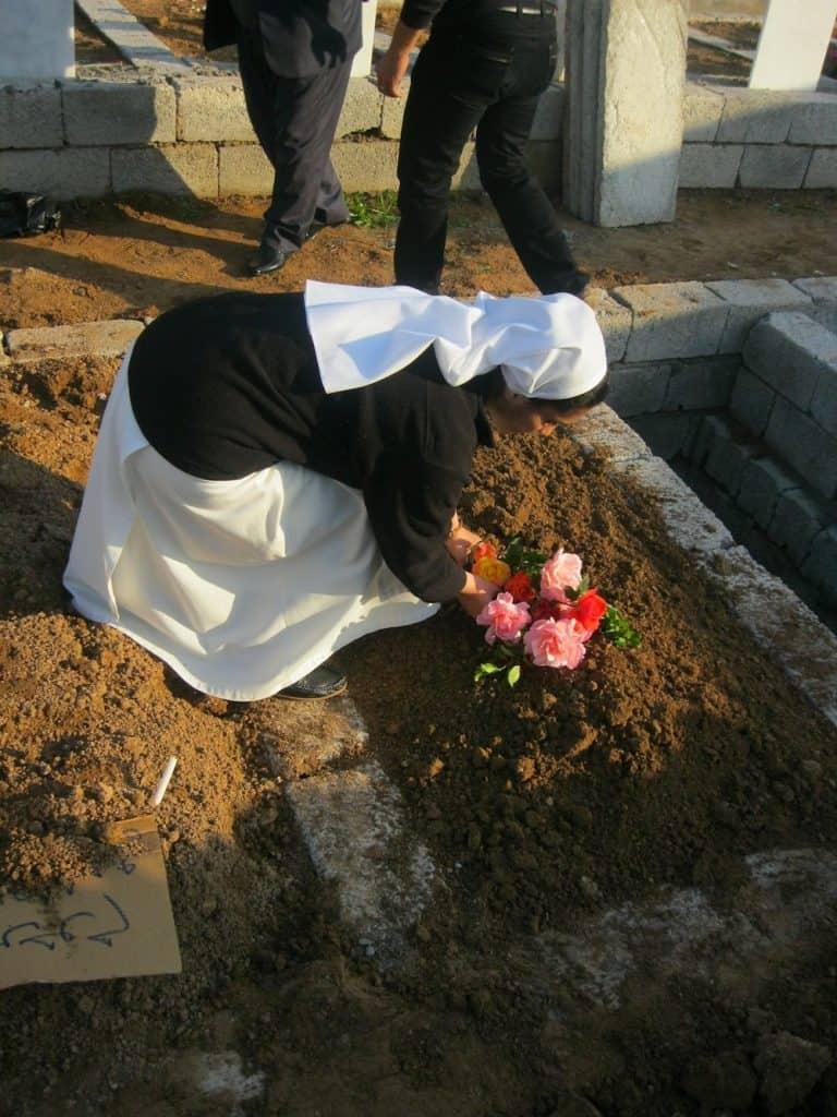 De jonge zr. Diana legt bloemen op het verse graf van zr. Najat Sheto.